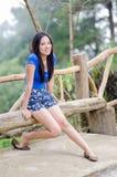 El sentarse y sonrisa tímidos jovenes de las mujeres de Asia en la silla larga de madera fotos de archivo libres de regalías