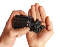 El ser humano vierte de las píldoras del negro de la botella en la palma, aislada Imagen de archivo libre de regalías