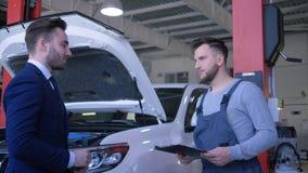 El servicio auto, dueño del consumidor entrega llaves del coche al trabajador del mecánico para la reparación profesional y sacud almacen de metraje de vídeo