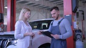 El servicio auto, propietario de coche entrega llaves del vehículo al hombre del técnico para la reparación y sacude las manos en almacen de metraje de vídeo