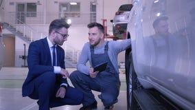 El servicio auto, reparador con la tableta comunica con el dueño cerca de la rueda del vehículo en la gasolinera almacen de video