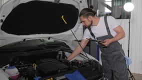 El servicio auto, sosteniendo la tableta digital en sus manos, mecánico se coloca cerca del automóvil abierto de la capilla, cabl metrajes