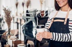 El servicio de Barista toma la taza de caf? awary en el caf? El delantal femenino asi?tico de la mezclilla del desgaste del baris imágenes de archivo libres de regalías