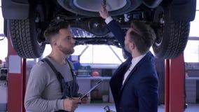 El servicio de coches, mecánico aconseja al cliente y hace que las notas en la situación del tablero debajo de hombres del vehícu metrajes