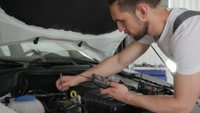 El servicio del coche del mecánico examina la máquina del sistema eléctrico almacen de video