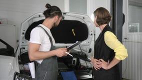 El servicio del coche, un mecánico joven coloca el automóvil siguiente almacen de metraje de vídeo