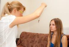 El sicoterapeuta de sexo femenino hipnotiza a un paciente femenino fotografía de archivo