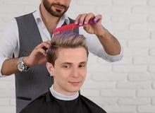 El sideview cosechado del peluquero que hacía la violeta del pelo coloreó el tono para el muchacho joven imagen de archivo libre de regalías