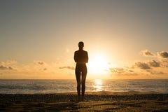 El silhuette humano solo en el mar costó la mirada de puesta del sol sobre un agua imágenes de archivo libres de regalías