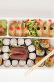 El sistema clasificado del sushi sirvió con los palillos en la caja blanca contra el fondo blanco Foto de archivo