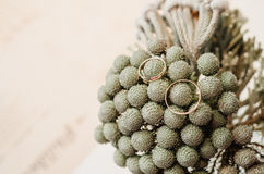El sistema de anillos de oro de la boda en ramo gris florece en florero estilo rústico, fondo beige fotografía de archivo