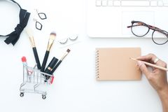El sistema de cepillos en carro de la compra, los accesorios de la mujer y el ordenador portátil en el fondo blanco con la mujer  Imágenes de archivo libres de regalías