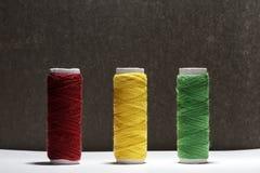 El sistema de colores en colores pastel rosca para coser en un fondo negro Sistema de hilos en estilo retro de las bobinas Acceso Imagen de archivo libre de regalías