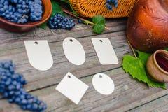 El sistema de diversas etiquetas pone al lado de cesta, del cuenco con las uvas, del tarro y de la taza con el vino en la madera  Foto de archivo libre de regalías