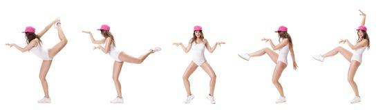 El sistema de jóvenes se divierte la mujer en el mono blanco y el baile rosado del sombrero en el fondo blanco Fotografía de archivo libre de regalías