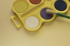 El sistema de la acuarela para los niños y el cepillo están en el fondo neutral Visión superior imagenes de archivo