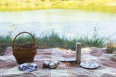 El sistema de la comida campestre, cubiertos del metal, termo, platea las tazas de té tela escocesa y servilleta marrones del lag Foto de archivo libre de regalías