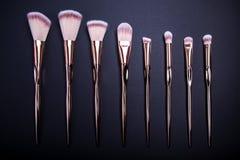 El sistema de los cepillos del maquillaje para el maquillaje hermoso mira en fondo negro Foto de archivo