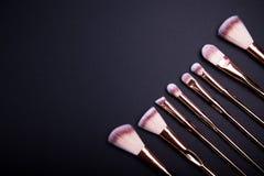 El sistema de los cepillos del maquillaje para el maquillaje hermoso mira en fondo negro Fotos de archivo