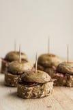 El sistema de Pintxos Pintxo, seta, curó el jamón y el pan en un tablero rústico, comida del país vasco Imágenes de archivo libres de regalías