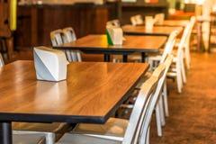 El sistema de sobremesa del mesa de comedor, madera y de las sillas blancas en el restaurante del hotel, adorna con la luz calien Fotos de archivo