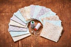 El sistema de telas en colores pastel arregló en círculo y las herramientas de costura en el centro Fotografía de archivo libre de regalías
