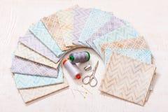 El sistema de telas en colores pastel arregló en círculo y las herramientas de costura en el centro Fotos de archivo
