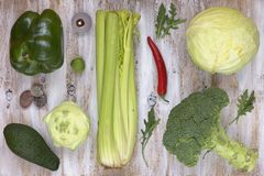 El sistema de verduras en blanco pintó el fondo de madera: colinabo, pimienta, col, bróculi, aguacate, rucola, coles de Bruselas, Imagen de archivo