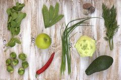 El sistema de verduras verdes en blanco pintó el fondo de madera: colinabo, aguacate, coles de Bruselas, manzana, pimienta, cebol Fotografía de archivo libre de regalías