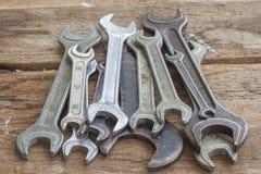 El sistema de viejas llaves inglesas miente en una tabla de madera Primer imagenes de archivo