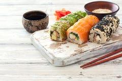 El sistema del sushi sirvió en un viejo tablero cuting imagen de archivo libre de regalías