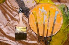 El sistema del vintage de los palillos de mezcla de Paint del artista y el cepillo están en una cubierta plástica fotos de archivo