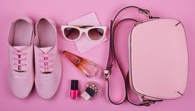 El sistema mínimo de las mujeres hermosas de complementos en un fondo rosado Imágenes de archivo libres de regalías