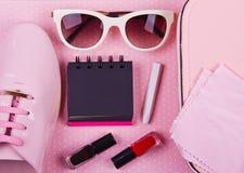 El sistema mínimo de las mujeres hermosas de complementos en un fondo rosado de los lunares Foto de archivo libre de regalías