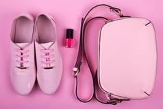 El sistema mínimo de las mujeres hermosas de complementos en un fondo rosado Foto de archivo libre de regalías