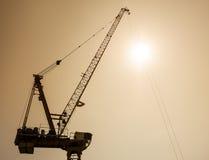 El sitio de Crane Equipment Construction siluetea el cielo de la puesta del sol Foto de archivo libre de regalías