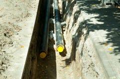 El sitio de la excavación a substituir la tubería subterráneo de la agua caliente abajo de la calle en el distrito de una ciudad  Fotos de archivo