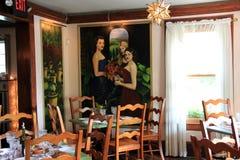 El sitio hermoso con las tablas y las sillas, alista para los comensales en el restaurante histórico de la casa de Mouzon, Sarato Fotos de archivo