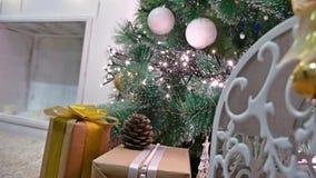 El sitio interior del árbol de los regalos de la Navidad y el Año Nuevo juega luces y la chimenea del centelleo Foto de archivo