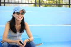 El skater de la mujer se sienta en música que escucha de las escaleras del skatepark Foto de archivo
