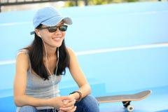 El skater de la mujer se sienta en música que escucha de las escaleras del skatepark Imagen de archivo libre de regalías