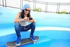 El skater de la mujer se sienta en música que escucha de las escaleras del skatepark Imagenes de archivo