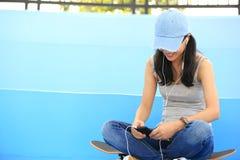 El skater de la mujer se sienta en música que escucha de las escaleras del skatepark Fotos de archivo