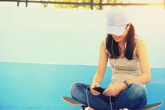 El skater de la mujer se sienta en música que escucha de las escaleras del skatepark Fotografía de archivo libre de regalías