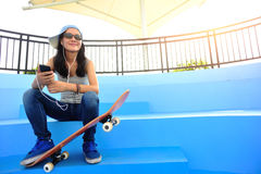El skater de la mujer se sienta en música que escucha de las escaleras del skatepark Fotografía de archivo