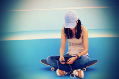 El skater de la mujer se sienta en música que escucha de las escaleras del skatepark Foto de archivo libre de regalías