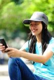 El skater de la mujer se sienta utiliza su teléfono móvil Fotos de archivo libres de regalías