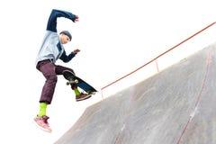 El skater del adolescente en el casquillo hace un truco con un salto en la rampa en el skatepark Patinador y rampa aislados encen Imágenes de archivo libres de regalías