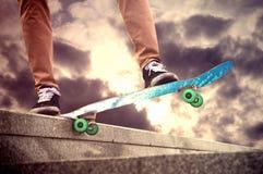 El skater hace movimientos hermosos del monopatín por la tarde encendido fotografía de archivo