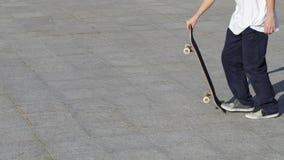 El skater irreconocible golpea para arriba un monopatín con el pie y toma un funcionamiento para ir rápidamente almacen de video